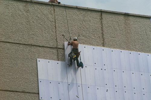 Промышленные альпинисты заняты утеплением фасада