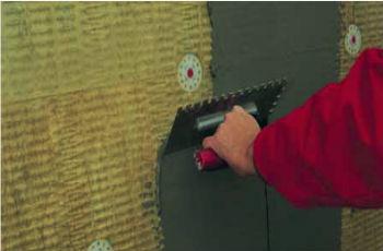 Нанесение первого слоя штукатурки на утепленную стену