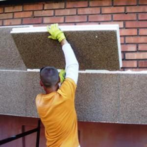 Крепление строителем армированного пенопласта на фасаде здания