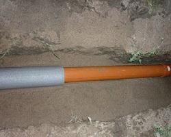 Утепленная скорлупой канализационная труба на дне траншеи